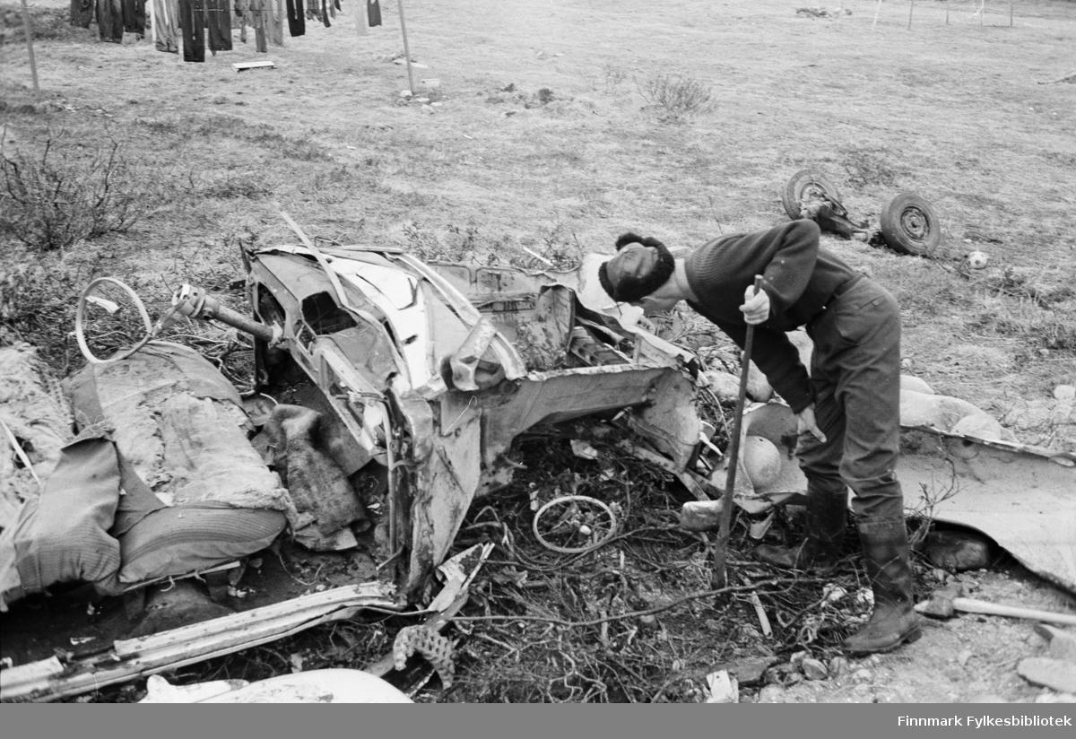 Serie med bilder fra Vadsø; trafikkulykker. Bilvrak. En person står og undersøker bilvraket. I bakgrunnen henger det en klesvask på snor.