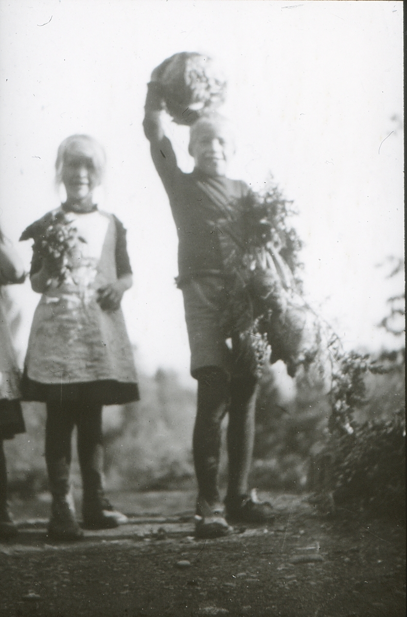 To barn, Per og søsteren, med blomsterbuketter.