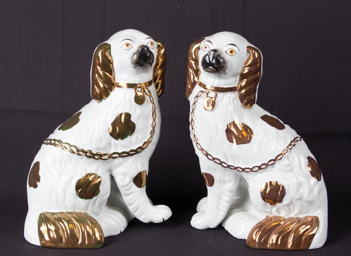 Porselensfigurer som forestiller to hunder som sitter, høyre og venstre, hvit med gulldekor og sorte snuter.