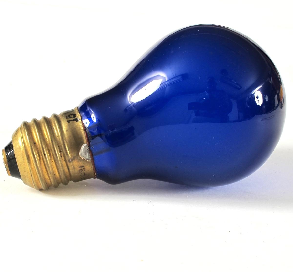 """Pæreformet lyspære, koboltblå med messingholder merket  blendingspære. Mssingholder merket 15 W-240V.  Pæren merket på toppen """"NOREG"""" to ganger."""