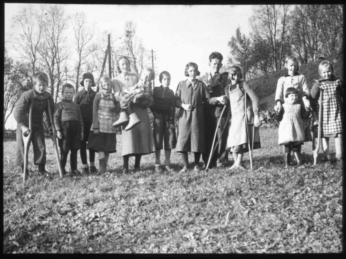 """""""234. Vanførehjemmet. Endel av de vanføre sammen med  vikarlærerinne frk. Kløften. (1936)"""" står det på glassplaten. Dette er sannsynligvis fra Bjerkely vanførehjem, opprettet av Finnemisjonen i 1913. Bildet er tatt i  1936 og er derfor tatt etter utvidelsen og påbyggingen av Bjerkely. (I boka Finnemisjoen er det beskrevet slik: """"Det var det første skolehjem for vanføre i Norge og det første som fikk statsbidrag. Stedet ble betydelig utvidet og påbygget i 1934, for å gi plass til flere barn. Bjerkly ble drevet som et skoleinternat hvor barna skulle få boklig og praktisk opplæring.""""). Mange som kom hit hadde hatt tuberkulose og polio som følge av sykdommen. Ungene som står med krykker er sannsynligvis angrepet med polio."""