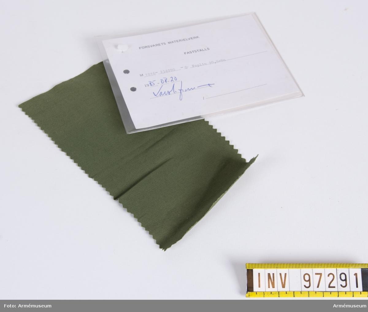 """Vidhängande modellapp med text: """"Försvarets materielverk. Fastställs. M 1016-234090-0. Poplin 90, Grön. 1985-08-20 (oläslig sign)"""""""