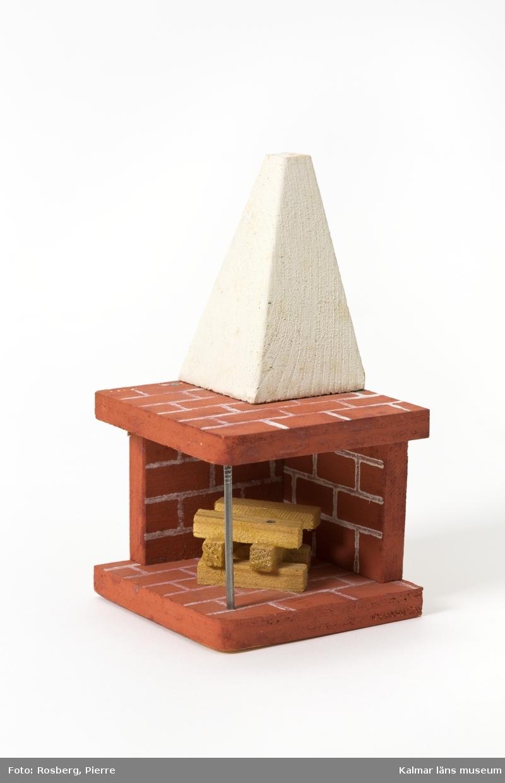 KLM 45437:4 Öppen spis, dockskåpsmöbel, av trä. Öppen spis målad som tegel i rött och vitt. Murstocken målad vit lik en putsad murstock. Spisen är öppen åt två håll och bärs i mitten av den öppna delen upp av en spik likt verklighetens förebilder som har ett metallstag. I spisen är sex vedträn staplade. Under spisen är skrivet 2.20.