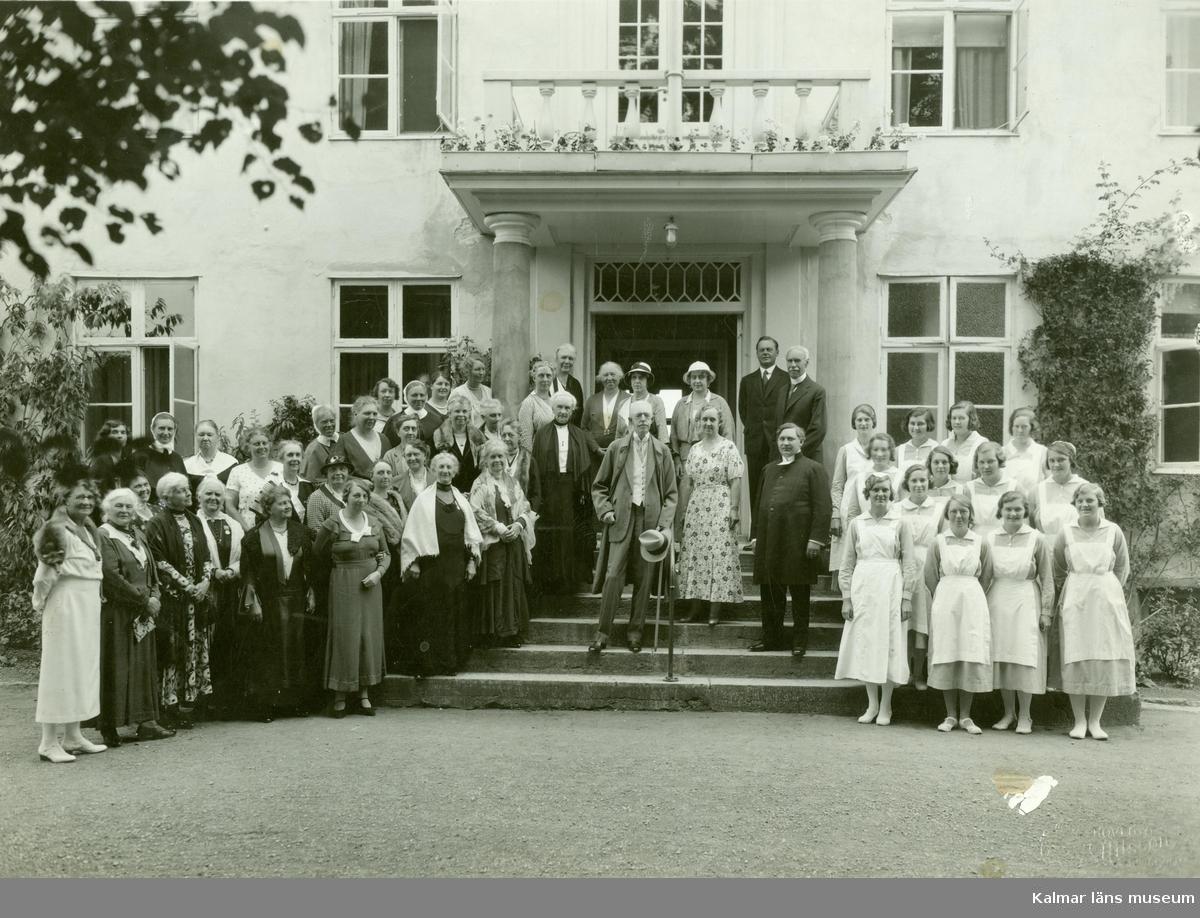 Kung Gustav V på trappan till drottning Viktorias vilohem år 1938, omgiven av personal och gäster.