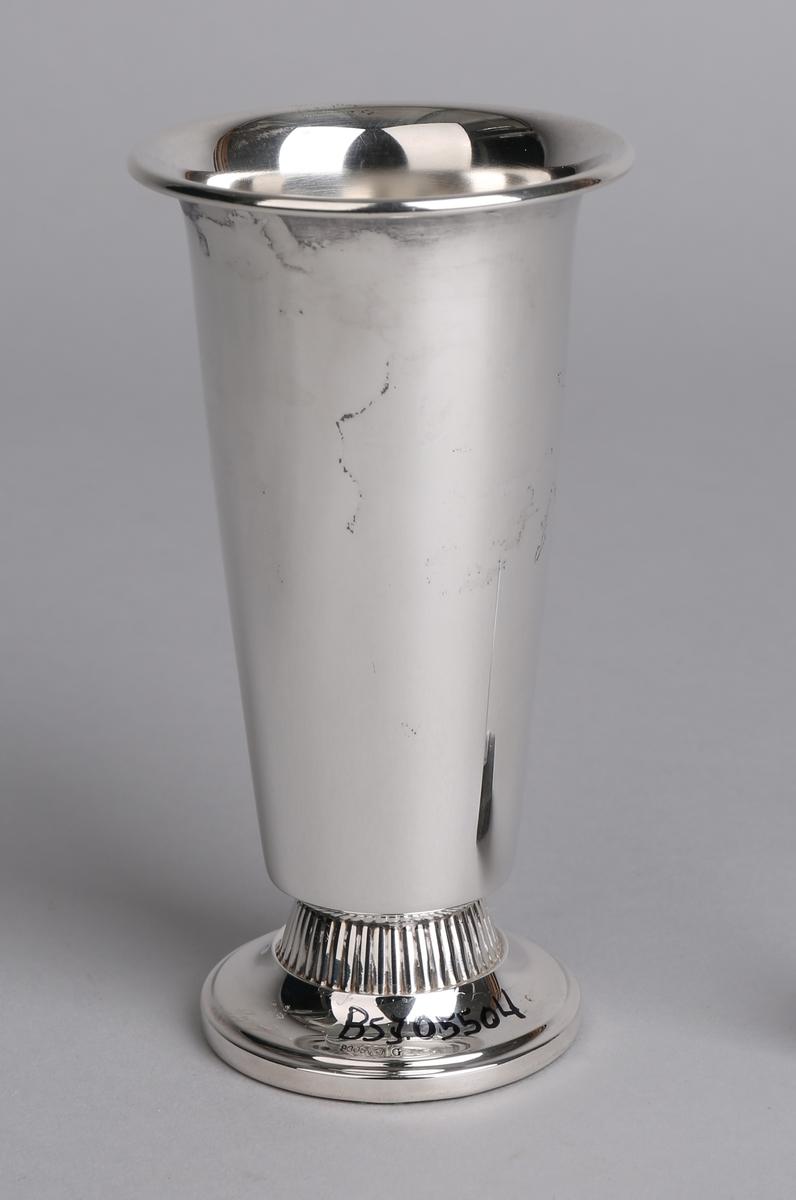 Sølvpokal på sokkel med tekst inngravert samt merke av en jordklode med emaljerte bånd rundt.