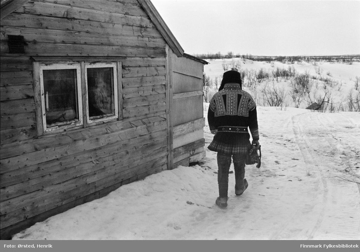 """Postfører Mathis Mathisen Buljo, bedre kjent som """"Post-Mathis"""" i samiske kretser, har kommet frem til en reindriftsenhet for å levere og hente post ute på Finnmarksvidda.   Fotograf Henrik Ørsteds bilder er tatt langs den 30 mil lange postruta som strakk seg fra Mieronjavre poståpneri til Náhpolsáiva, videre til Bavtajohka, innover til øvre Anárjohka nasjonalpark som grenser til Finland – og ruta dekket nærmere 30 reindriftsenheter. Ørsted fulgte «Post-Mathis», Mathis Mathisen Buljo som dekket et imponerende område med omtrent 30.000 dyr og reingjetere som stadig var ute i terrenget og i forflytning. Dette var landets lengste postrute og postlevering under krevende vær- og føreforhold var beregnet til 2 dager. Bildene gir et unikt innblikk i samisk reindriftskultur på 1970-tallet. Fotograf Henrik Ørsted har donert ca. 1800 negativer og lysbilder til Finnmark Fylkesbibliotek i 2010."""