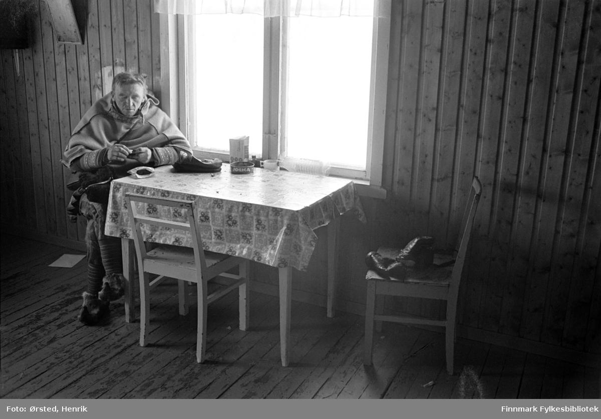 """Postfører Mathis Mathisen Buljo, bedre kjent som """"Post-Mathis"""" i samiske kretser, sitter og venter ved kjøkkenbordet i et hus langs postruta. Kanskje venter han på at postkundene skal komme inn fra arbeid på vidda?   Fotograf Henrik Ørsteds bilder er tatt langs den 30 mil lange postruta som strakk seg fra Mieronjavre poståpneri til Náhpolsáiva, videre til Bavtajohka, innover til øvre Anárjohka nasjonalpark som grenser til Finland – og ruta dekket nærmere 30 reindriftsenheter. Ørsted fulgte «Post-Mathis», Mathis Mathisen Buljo som dekket et imponerende område med omtrent 30.000 dyr og reingjetere som stadig var ute i terrenget og i forflytning. Dette var landets lengste postrute og postlevering under krevende vær- og føreforhold var beregnet til 2 dager. Bildene gir et unikt innblikk i samisk reindriftskultur på 1970-tallet. Fotograf Henrik Ørsted har donert ca. 1800 negativer og lysbilder til Finnmark Fylkesbibliotek i 2010."""