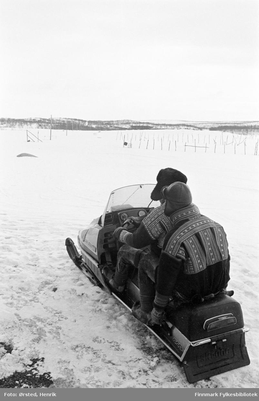 To reindriftssamer i kofter på skuter fotografert i arbeid ute på Finnmarksvidda.   Fotograf Henrik Ørsteds bilder er tatt langs den 30 mil lange postruta som strakk seg fra Mieronjavre poståpneri til Náhpolsáiva, videre til Bavtajohka, innover til øvre Anárjohka nasjonalpark som grenser til Finland – og ruta dekket nærmere 30 reindriftsenheter. Ørsted fulgte «Post-Mathis», Mathis Mathisen Buljo som dekket et imponerende område med omtrent 30.000 dyr og reingjetere som stadig var ute i terrenget og i forflytning. Dette var landets lengste postrute og postlevering under krevende vær- og føreforhold var beregnet til 2 dager. Bildene gir et unikt innblikk i samisk reindriftskultur på 1970-tallet. Fotograf Henrik Ørsted har donert ca. 1800 negativer og lysbilder til Finnmark Fylkesbibliotek i 2010.