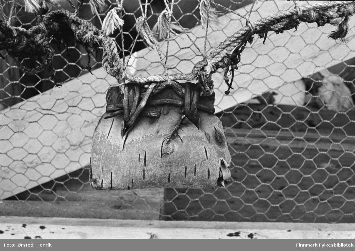 """Nærbilde av veske laget av bjørkenever og festet på et gjerde ved  en samisk siida. Bildet er tatt langs postruta til postfører Mathis Mathisen Buljo, bedre kjent som """"Post-Mathis"""" blant samene. Det nordsamiske uttrykket siida har flere ulike betydninger, blant annet fellesskap og hjem. Neverveska er muligens til å legge post eller beskjeder i når reindriftssamene er ute på vidda?   Muligens er dette en samisk kont eller neverkont? """"Kont eller neverkont er en avstivet ransel eller veske til å bære på ryggen, som tradisjonelt har blitt laget av bjørkenever. En slik lett, hard, ofte kasseformet ryggsekk av flettverk, og gjerne med lokk og bunn av tre, beskytter innholdet mot støt, og til en viss grad også mot dårlig vær. Betegnelsen kont har også vært brukt om ulike typer kurver.""""  Fotograf Henrik Ørsteds bilder er tatt langs den 30 mil lange postruta som strakk seg fra Mieronjavre poståpneri til Náhpolsáiva, videre til Bavtajohka, innover til øvre Anárjohka nasjonalpark som grenser til Finland – og ruta dekket nærmere 30 reindriftsenheter. Ørsted fulgte «Post-Mathis», Mathis Mathisen Buljo som dekket et imponerende område med omtrent 30.000 dyr og reingjetere som stadig var ute i terrenget og i forflytning. Dette var landets lengste postrute og postlevering under krevende vær- og føreforhold var beregnet til 2 dager. Bildene gir et unikt innblikk i samisk reindriftskultur på 1970-tallet. Fotograf Henrik Ørsted har donert ca. 1800 negativer og lysbilder til Finnmark Fylkesbibliotek i 2010."""