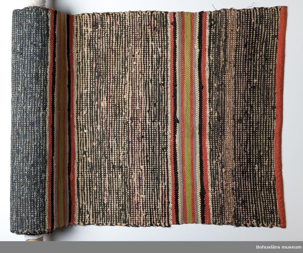 En av de sex sammanhörande trasmattor lagda kant i kant med varandra på lilla salens golv. Äldre än uppsättningen UM021224:001-006, som troligen ersatt denna uppsättning.  Samtliga med samma mönsterbård. Bredare parti med huvudsakligen vit och svart/grått inslag, däremellan smalare partier i rött, grönt, vitt, blågrått. Kantade i kortändarna med rött bomullstyg. Mer sliten, tvättad och blekt än UM021224, för övrigt relativt likartad.  Litteratur: Kerstin Ankert/Ingrid Frankow: Den svenska trasmattan, en kulturhistoria, Prisma 2003.