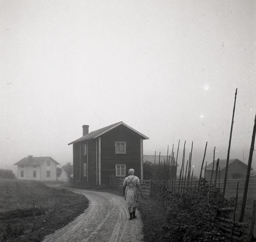 En kvinna vandrar på en grusväg mot några gårdar i dimma, Knåda, Edsbyn september 1949.