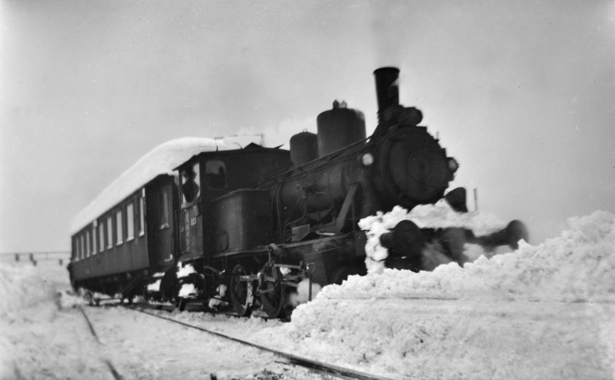 Snøryddingsmannskaper og snøryddingstog trukket av damplokomotiv type 25a nr. 223 på Trondheim stasjon.