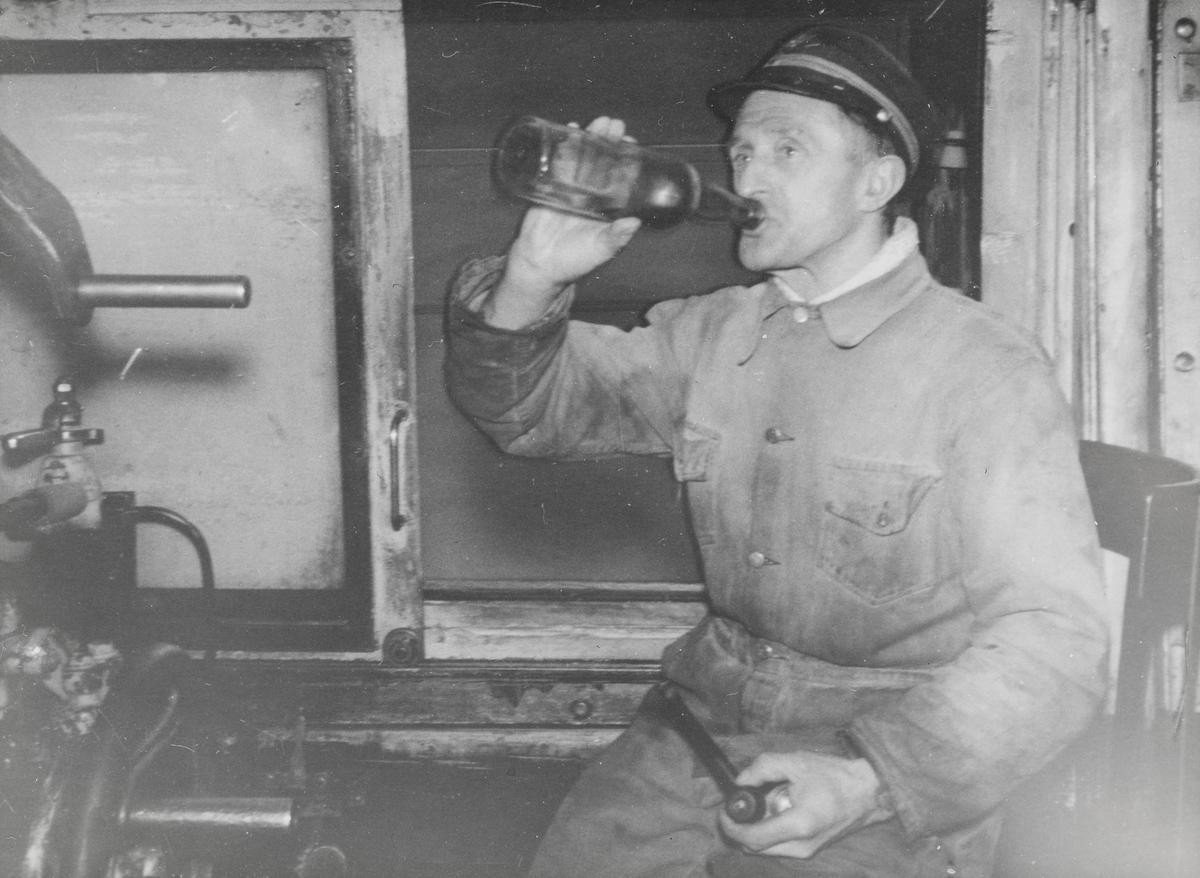 Lokomotivfører Iver Skjerdingstad på førerplassen på damplokomotiv type 63a.