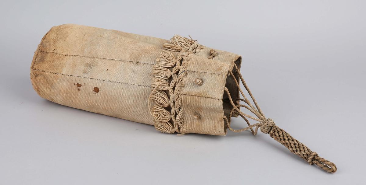 Seilmakerpose som inneholder diverse seilmakerverktøy. Seilmakerpose i hvit seilduk med frynser rundt øverste kant og flettet tau.  Posen inneholder: A: Prim av tre (stor), B: Prim av tre (mindre) C. Klekyle (Stor), D: Klekyle (middels), E. Klekyle (liten) F. Seiltræprim, G: Merelspiker (av stål), H. Trestokk (for wirerbensling) J. Fetthorn (med seilmakernåler ?) K: Sømstryker, L: Seilhanske, M: Prim (av metall med tre håndtak).