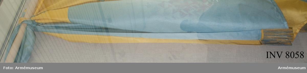 Kravatt till fana, Arméns underofficersskola AUS. Ett band sytt hälften blått, hälften gult på längden. I ändarna en frans, 100 mm bred i gult silke blandat gult och blått. Bandet har samma ljusa blå färg som fanan.
