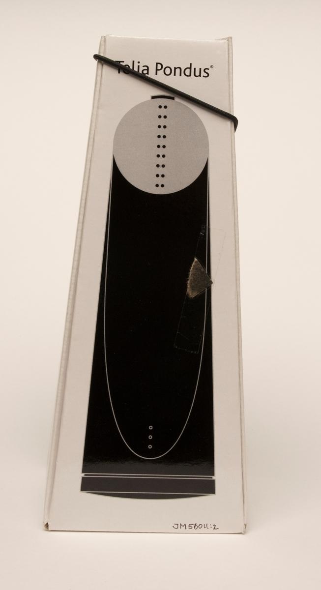 """Telefon, stående modell för bordsplacering, av svart och grå plast, i originalförpackning. Telefonen är trådbunden och försedd med svart plastsladd. I förpackningen finns en bruksanvisning av papper   Originalförpackningen är av wellpapp, vit utvändigt, med hög avsmalnande form. De fyra sidorna fälls ut vid öppning. Sidorna hålls ihop med svart gummisnodd i toppen. På originalförpackningen står tryckt: """"Vissa telefoner är liksom bara telefoner. Men Telia Pondus är något mer. Den är enastående. Det både ser och känner man vid första anblicken. Finesser erbjuds också: två snabbval och repetition av senste slaget nummer.""""  JM 56011:1 telefon JM 56011:2 förpackning JM 56011:3 bruksanvisning"""