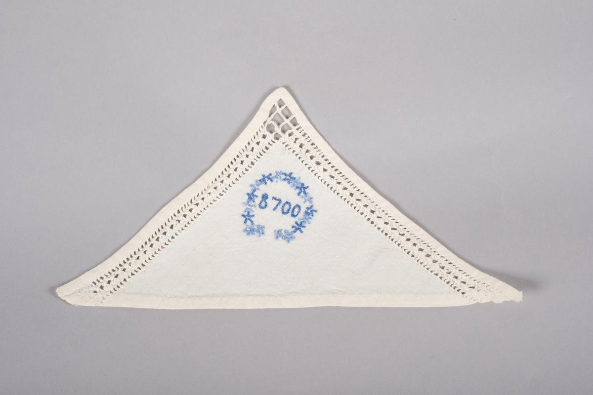 """Hvit trekant lommetørkle med hullbroderier langs kanten og en brodert blå blomsterkrans rundt """"8700"""", fangenummeret til Grete Wold."""
