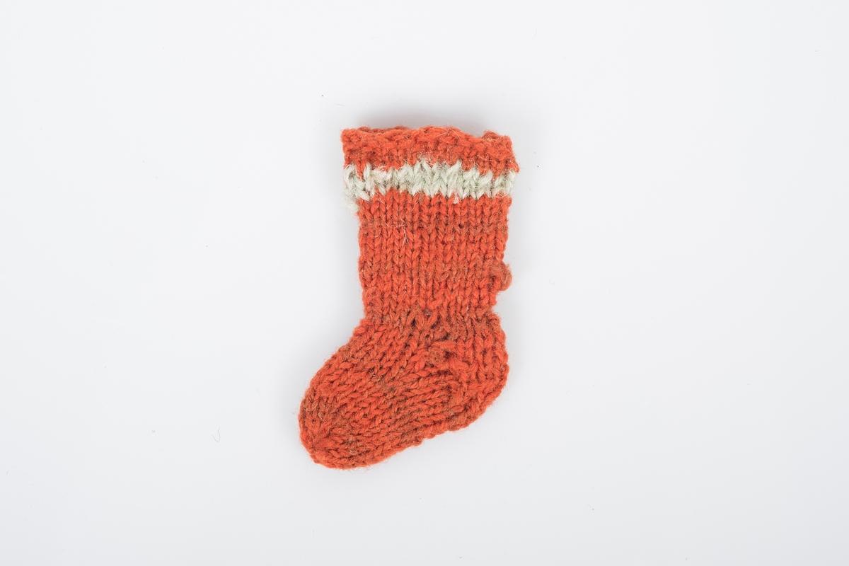 1. av et par bittesmå strikkede ullsokker. Sokkene er oransjerøde med en lys stripe øverst og nøen brunrøde striper lenger ned.
