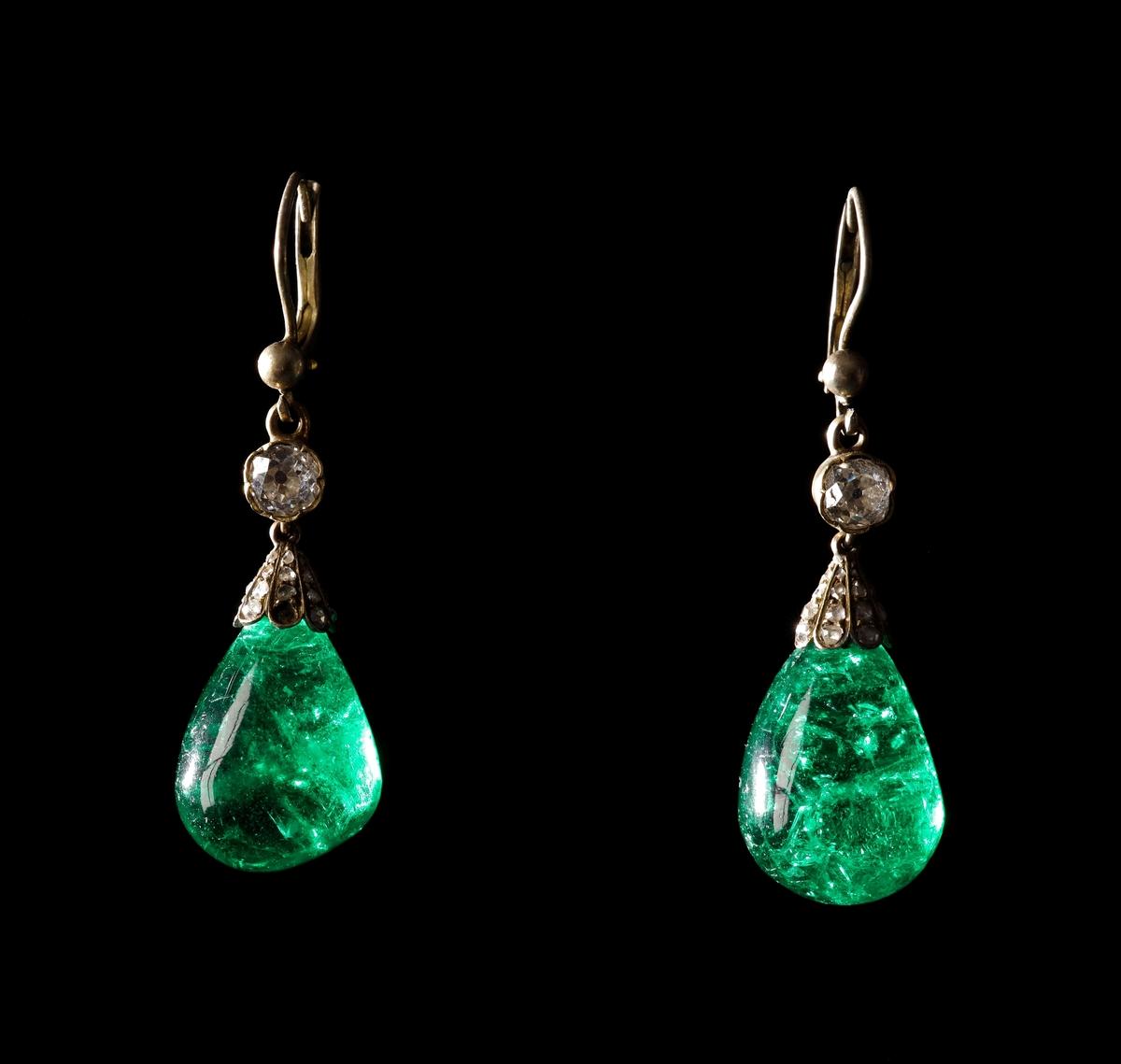 Örhängen bestående av två gröna, droppformade, columbianska cabochonslipade smaragder samt guld och diamanter i fästena.   Inskrivet i huvudkatalogen 1998.