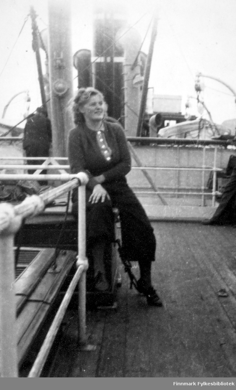 """På tur med """"Midnattssol"""" til Tromsø. Gerd Klemetsen, 1946. Hurtigruta Midnattssol. Gerd er kledd i vide langbukser med topp med knapper og strikkejakke.  Familiealbum tilhørende familien Klemetsen. Utlånt av Trygve Klemetsen. Periode: 1930-1960."""