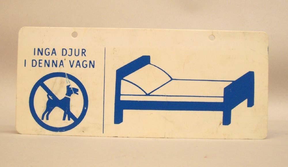 """Rektangulär plastskylt med blått pictogram på vit botten. Skylten är en liggvagnsskylt, och visar en stiliserad teckning av en blå säng. I skyltens ena hörn en blå förbudsskylt med en hund och texten: """"Inga djur i denna vagn"""". Andra sidan är identisk. Två små hål för upphängning i övre kanten."""