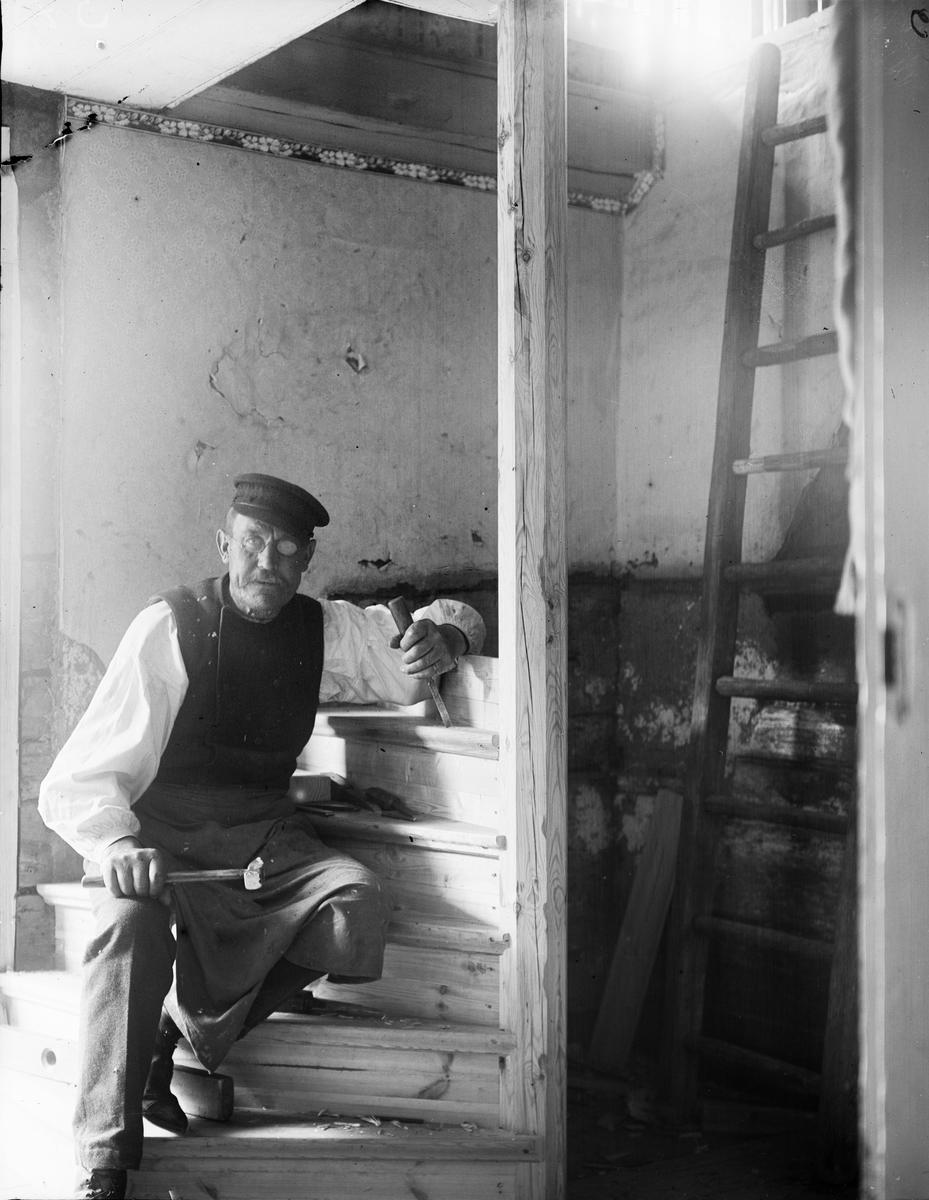 Byggnadssnickare sitter i trapp under konstruktion, Uppland