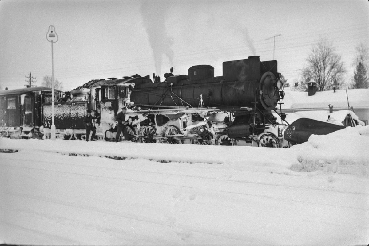 Persontog fra Oslo Ø til Trondheim over Røros, Pt. 301, på Rena stasjon. Toget trekkes av damplokomotiv type 26a nr. 215.