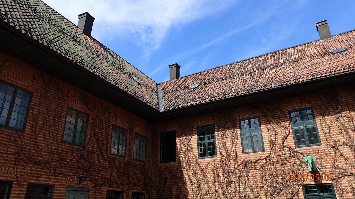 """1714 Gården ble gjenreist på museet i 1928 for å tjene som utstillingsbygning. Den er en delvis kopi av Dronningensgt. 15. Fasaden er i hovedtrekk som de opprinnelige, men i bygningens indre er det bare trapperommet og hjørnerommene i begge etasjer som er overført til museet. Ankerjernene på fasaden - Ao 1714 TESGMMD - viser initialene til byggherren Tøger Eriksen Grøn og hans hustru Margrethe Mogensdatter, datter av Mogens Lauritsen på Linderud. Ankerjernene av smijern er forbundet med bjelkene i etasjeskillet og hindrer at disse mister festet i veggen. I tillegg til det gjenreiste hovedhuset har det vært en sidefløy med uthusfunksjoner. I 1737 ble Dronningensgate 15 kjøpt av general Hans Jacob Arnold. I 1749 bodde kong Fredrik V hos ham under besøket i Chrisiania. Fra Arnolds tid stammer den elegante barokktrappen i trapperommet, samt panel, dører og himlinger i hjørnerommene. Himlingene har vakre stukkarbeider med allegoriske fremstillinger, antagelig laget i 1752 av Ole Trulsen Svartz. Staten overtok gården i 1760, og den ble embetsbolig for kommanderende general og kontor for Generalitetskollegiet. Bygningen lå i det kvartalet som 1814 ble tatt til lokaler for statsadministrasjonen og kalles også """"Det gamle finansdepartementet"""". I nabogården, som til 1822 huset Katedralskolen, lå salene som 1814 til 1866 ble brukt av stortinget (NF326/NF327). Bygningen huser nå Norsk farmasihistorisk Museum med officient fra apoteket """"Hjorten"""" i Grønland 10, fra 1861. På motsatt side av gårdsplassen ligger apotekerhagen, en urtehage med eksempler på medisinske planter som har vært dyrket i Norge i eldre tid. Fasaden med skiftevis gule og røde striper var høyeste mote i Christiania i første halvdel av 1700-tallet; noe som hadde bakgrunn i datidens mureteknikk. Det ble brukt importert tegl hvor løpersiden var gulfarget, mens koppsiden var rød. Ved oppmuring i kryssforband oppstod stripeeffekten av seg selv. Moten fikk slik oppslutning at man også malte striper på mur av ensfarget"""