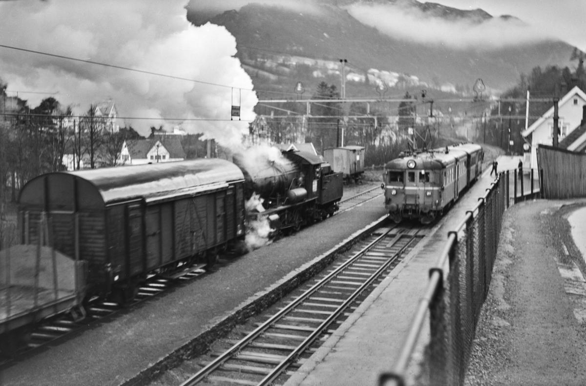 Kryssing på Fjøsanger stasjon mellom lokaltog reting Voss, tog 624, og kipptog til Bergen. Kipptoget trekkes av damplokomotiv type 33a nr. 300. I lokaltoget elektrisk motorvogn Bmeo 65 og styrevogn BFo4b.