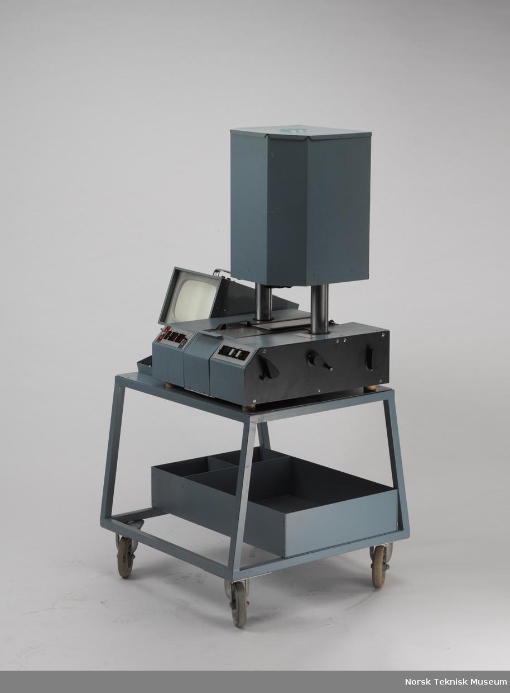 Apparatet er ikke komplett med orignale deler. Monitoren Disa er tilpasset bruk og har fått en ny metallplate som understøtte. Det originale speilet som ble brukt, mangler. Gjenstanden står på et originalt trillebord og har en kasse under med diverse tilkoblingsledninger.  En luke i bakkant av apparatet mangler.