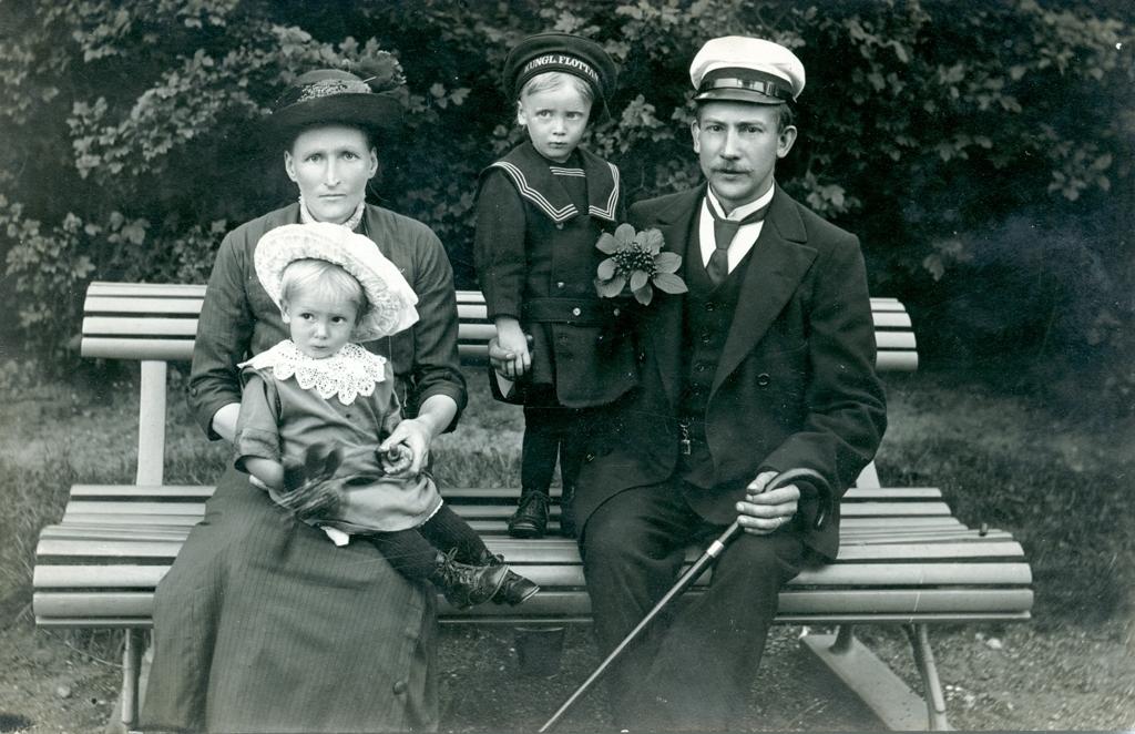 Familjen Träff sitter på en parkbänk. Mariana, Helge, Agnes och Oskar.