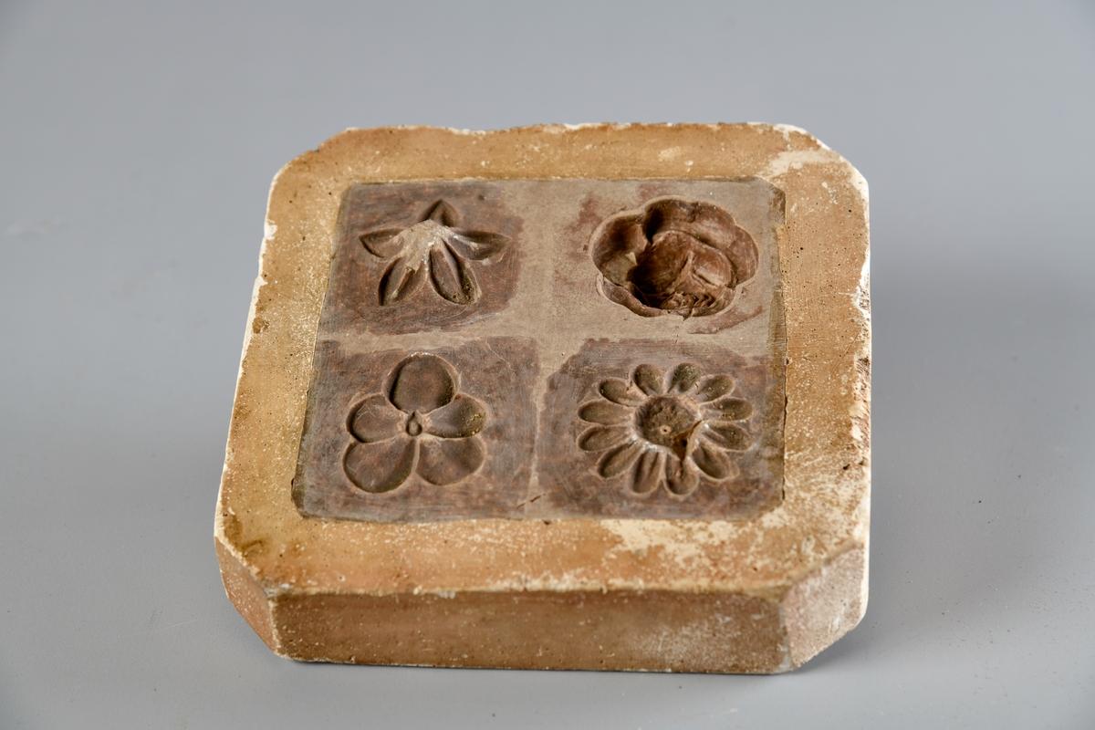 Kvadratisk gipsform med avrundete hjørner. Formmotivet er fire ulike blomster.
