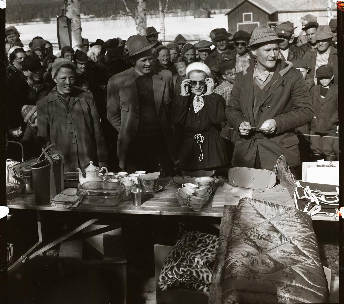 Pristagare vid pimpeltävling med 330 deltagare på Hölesjön 22 april 1956. Publik och deltagare tittar på föremålen på prisbordet.