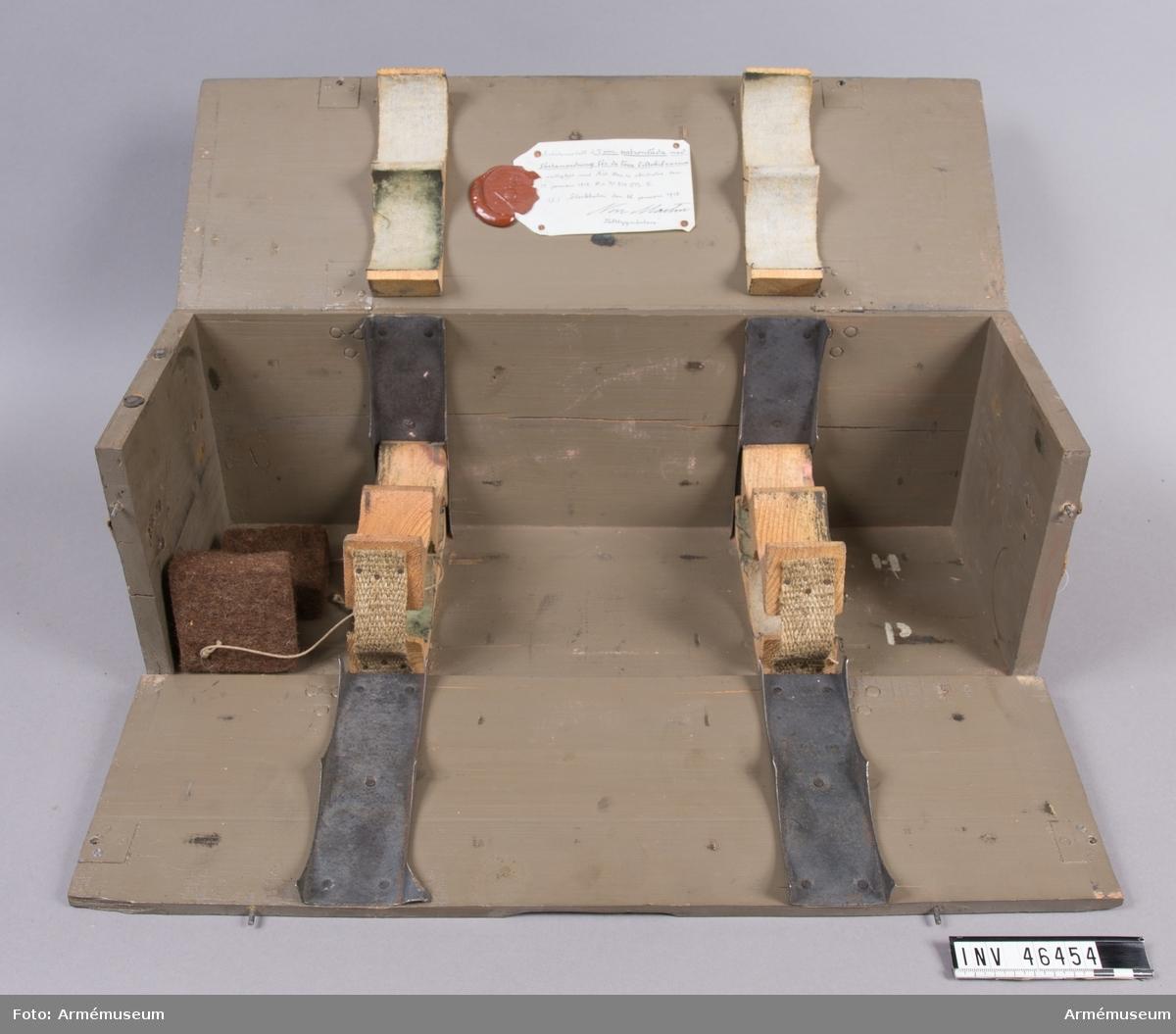 Grupp E V. Arbetsmodell å 7 cm patronlåda med fästanordning för de lösa filtskivorna. Enligt Artilleridepartementets skrivelse den 17 januari 1913. Lådan är tom.