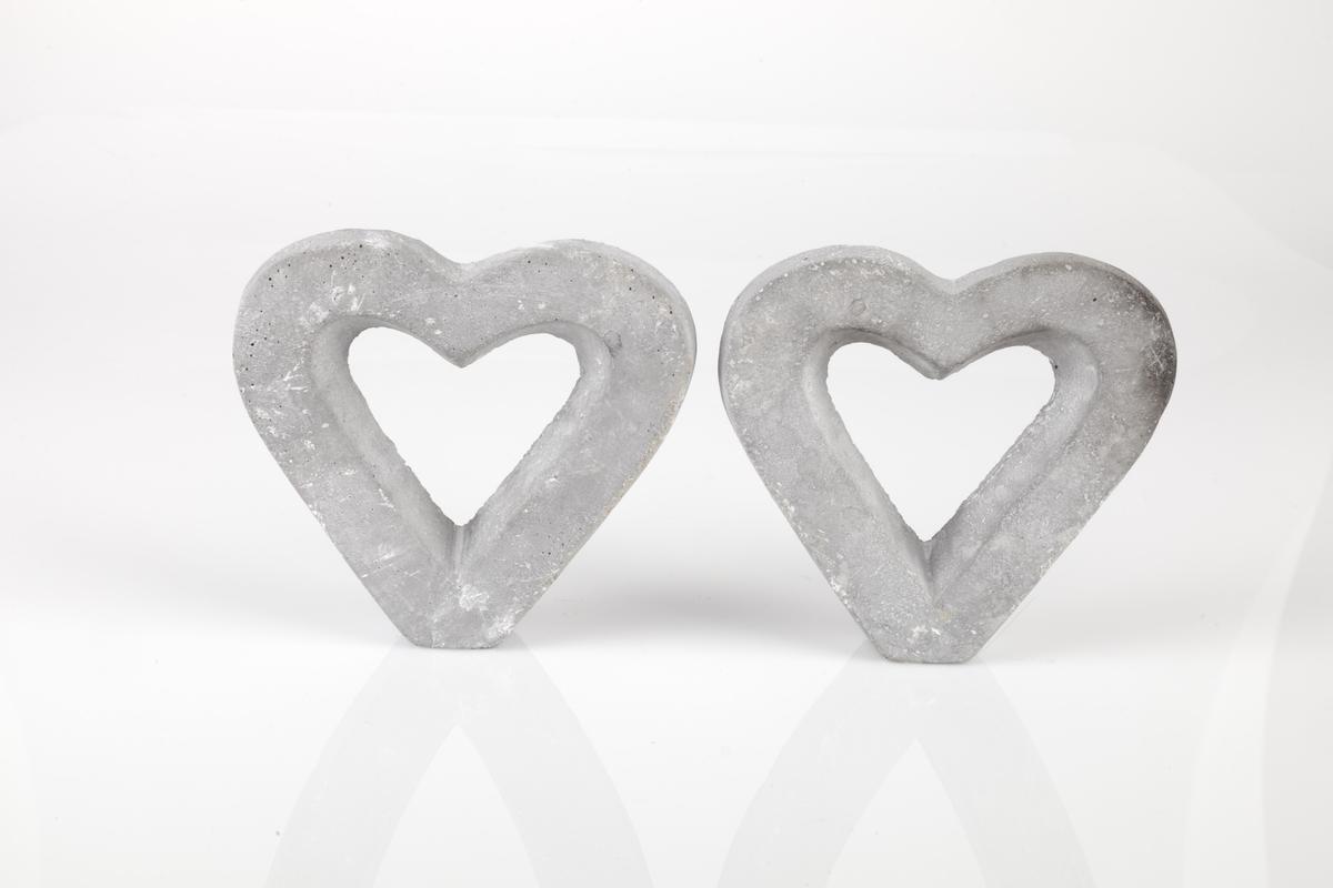 Pyntegjenstander innsamlet etter terrorhandlingen 22. juli 2011 fra minnesmarkeringene i Lillestrøm.   A-B: To hjerter som er støpt i grå betong. Hjertene har hjerteformet hull i midten. Åpningen er formet slik at den er videre i front en bak. Det skaper en fin dybdefølelse. Overflaten er både rå og glatt. Dvs. den virker både rustikk, porøs og bastant og glatt. Baksiden er flat og mer ru enn forsiden. Fargen er ganske gjevnt grå, men med noen hvite og noen mørkere grå innslag.  Klistrelapper fra butikken er limt på undersiden, basen der de står, men på A er det meste av lappen revet bort. A ser også ut til å ha fått sotskade; den er noe sort øverst på den høyre siden.