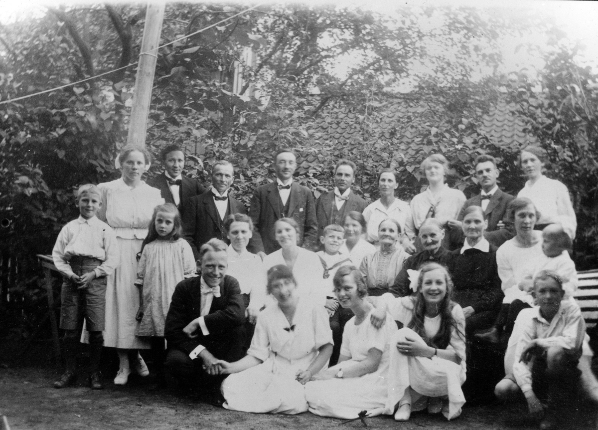 Gruppbild av män, kvinnor och barn i en trädgård.
