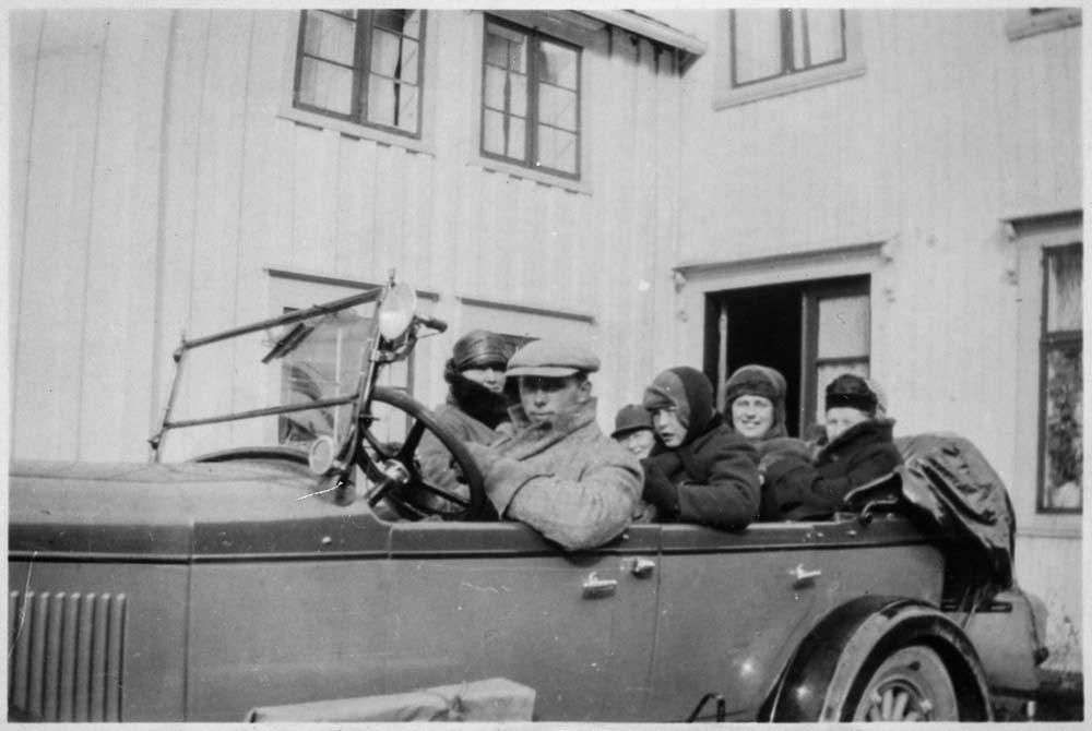 Flere personer i en Chrysler Roadster (1928 modell?). W-27 registrert på Gunnar Wikborg Vik som også er sjåføren på bildet. Roadster var betegnelsen på et åpent to-dørs to-seters karosseri. Evt. med 2 plasser i svigermorsete i avrundet bakende, som alternativ til bagasjerom. Dette er en åpen fire-dørs 5-seter (kanskje 7?), som gjerne ble kalt phaeton (=solvogn) på denne tida.