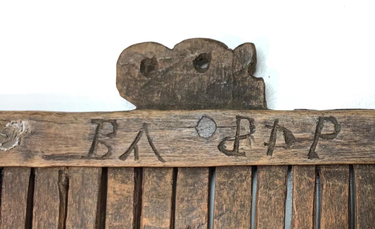 Brun båndgrind av tre med 27 (antagelig 28 originalt) spiler som har et enkelt hull i midten, samt dekorativt skåret utstikker med tre hull ut fra midten av den ene langsiden.