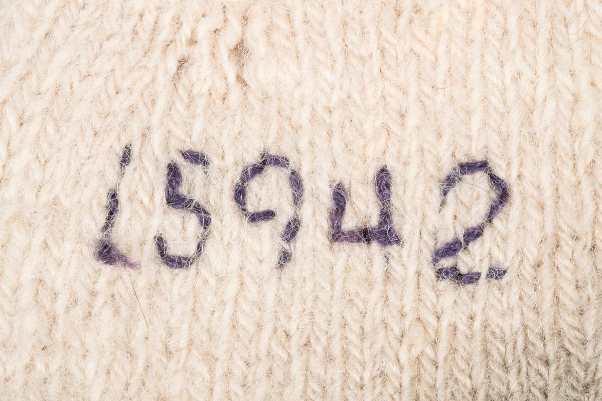 En strikket vott. Votten er strikket i hvitt garn. Den har en strikket snor fra åpningskanten, som brukes til å knyte den sammen med den andre votten når de ikke er i bruk. Den har brodert fangenummer (15942).