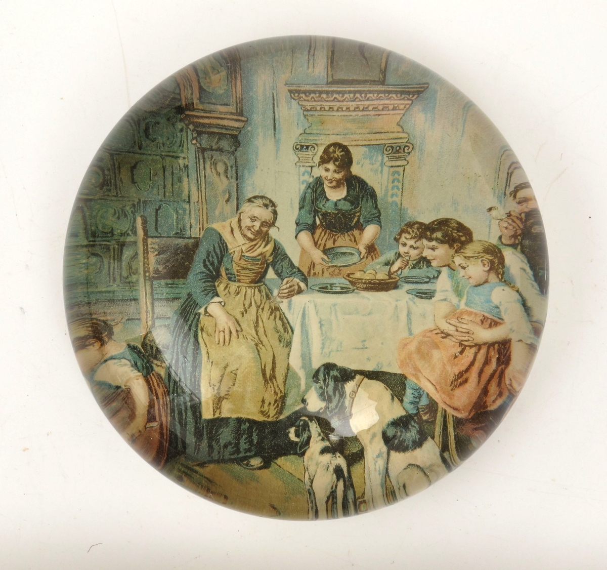 Familie rundt et spisebord med hvit duk, to hunder i  forgrunnen. Interiør med kamin, vindu tv.