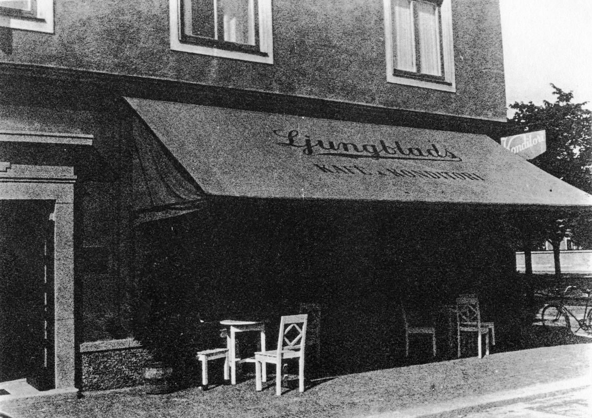 """Gatuvy av Ljungblads konditoris med en stor markis med text """"Lingblads Kafé Konditori"""" som sträcker sig över uteserveringen. Konditoriet låg senare på Lilla torget i kvarteret Pelikan."""