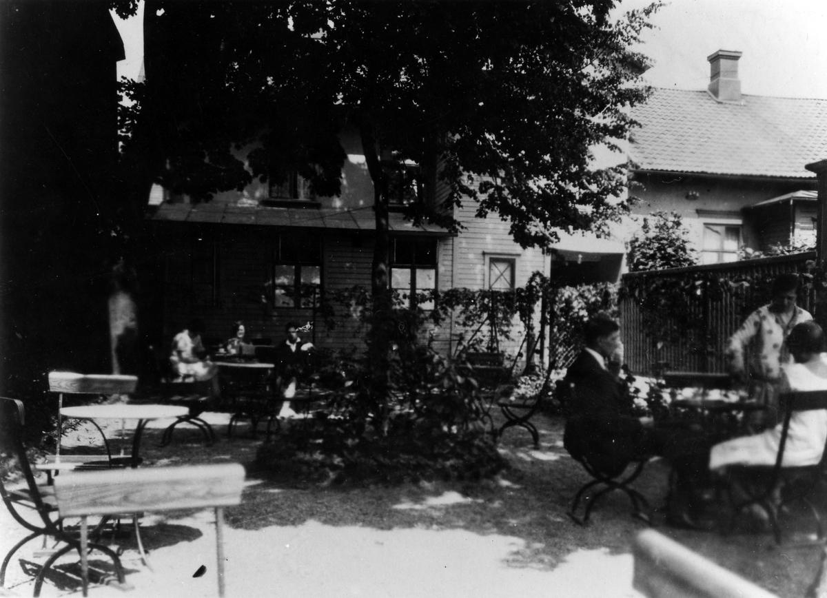 Bilden visar Ljungblads gårdsservering med gäster som sitter runt borden.
