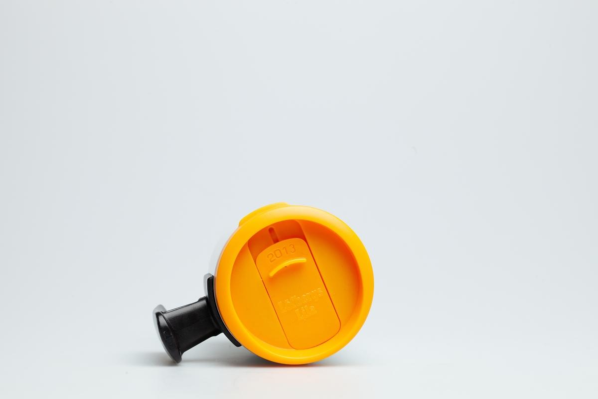 Et oransje skrulokk til en Statoilkopp fra 2013. En mekanisme i lokket kan åpne og lukke for et lite hull, der kan man drikke kaffe gjennom. På skrulokket står det 2013 og Löfbergs Lila.