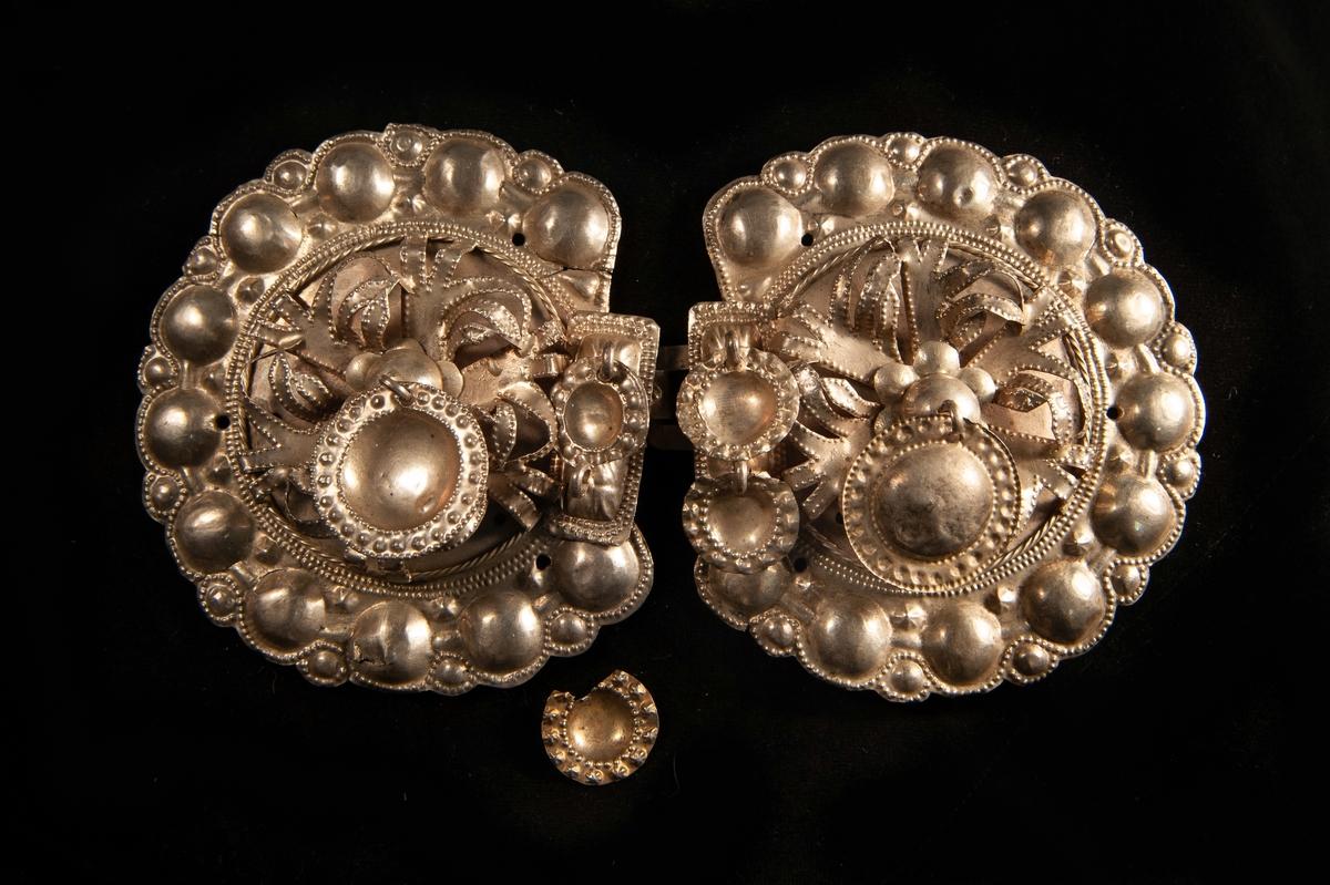 """Ett stort tröjspänne av ciselerat silver med pålagda """"klippta"""" ornament i upphöjt arbete (bladform) och en blomma i mitten. Behängd med 3 delvis ciselerade små, rundaplattor av silver.  Har en hyska som fästes i haken på JM.19959:2."""