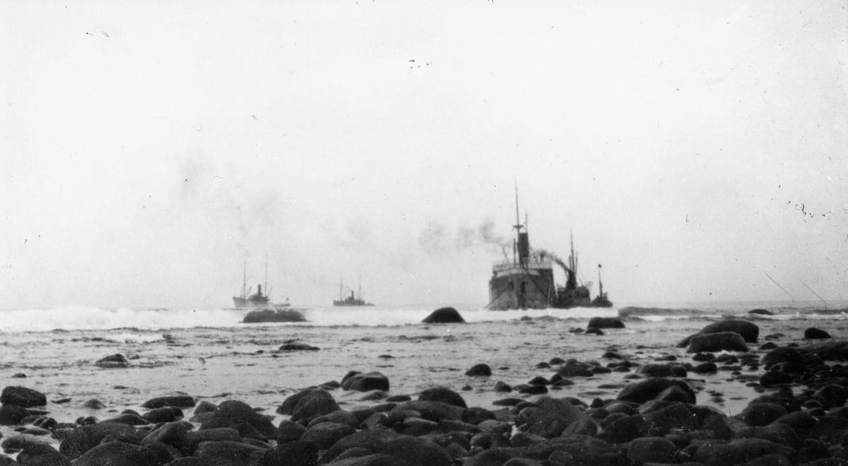 5 dampskip liggende ved brenningene utfor en steinete kyst.