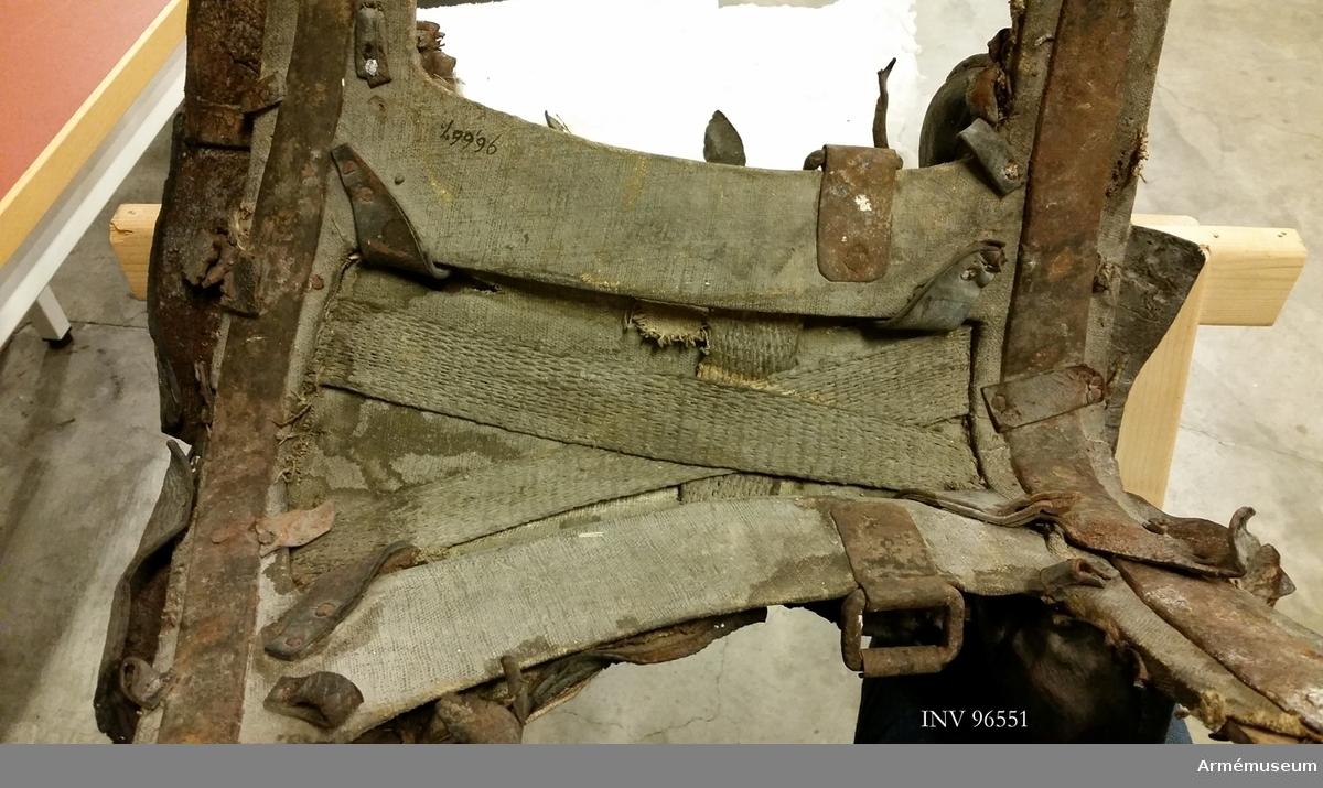 Bomsadel klädd med läder. Stomme av trä förstärkt med limmad väv, näver samt järnbleck. Det bakre blecket följer hela böjningen av bommen och har en sölja för svansrem. I de längsgående styckena är järnkrampor för stiglädren fästa. Sadelgjord är fäst i stommen för att bära upp sitsen. Sitsen saknas helt och endast foderväven återstår. Bakbommen består av en vävklädd träkärna, stoppad med någon typ av växtfiber och djurhår, samt en klädsel bestående av ett lager väv och ett lager läder. Väv och läder är sammanstickade med stoppning emellan i diagonala linjer. Bakkanten är formad som en liten vulst. Frambommarna är tvådelade och består av en mindre bit utan stoppning och en större puta på insidan. Längs framkanten på bommarna är en rad mässingstennlikor fästa såsom på bakkanten av bakbommen. På den plats där sadelknappen troligen har suttit är läderklädseln öppen.  Sadelkappor saknas och det tycks möjligt att dessa har skurits bort avsiktligt. Rester finns vid sadelns framkant där man kan se att kapporna kantats av dekor bestående av pressade och stickade linjer Bossorna är också borta. 2015-10-19 KTS