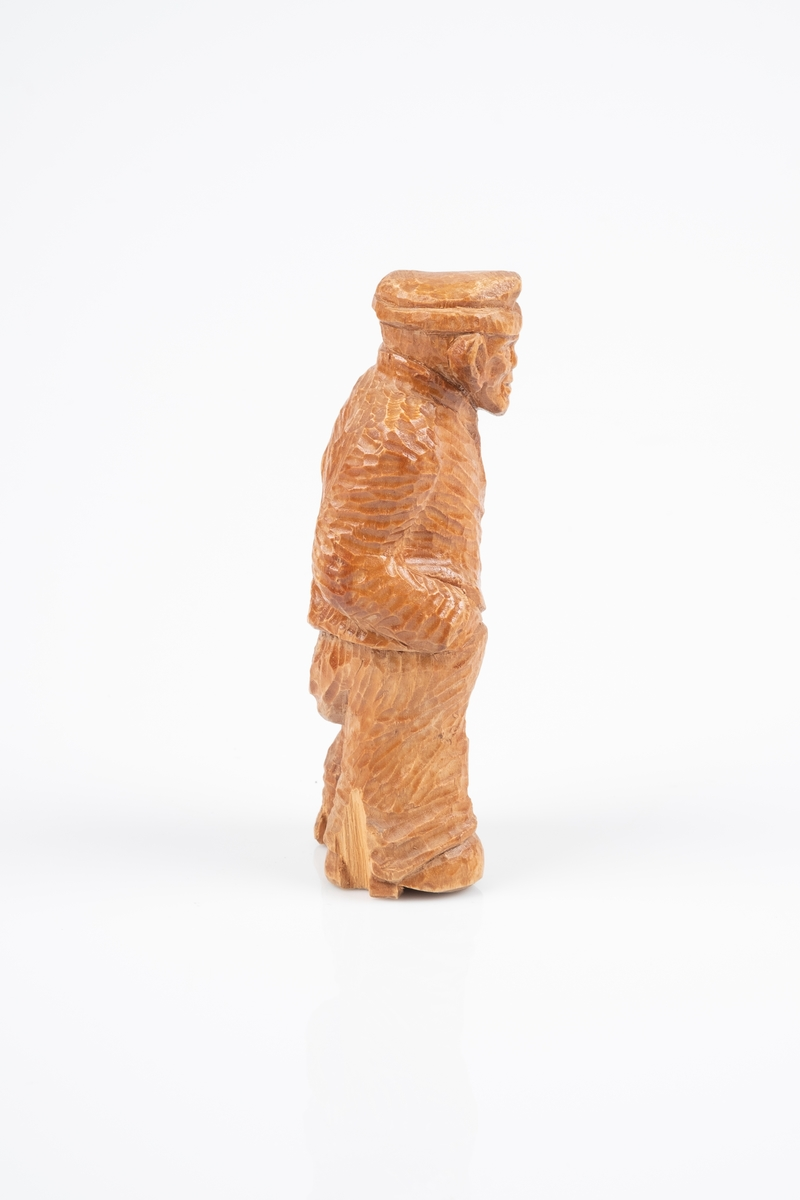 Utskåret trefigur som forestiller en mannlig fange med fangedrakt. Han står med hendene i bukselomma. På undersiden av figuren er et fangenummer skrevet på med blyant.