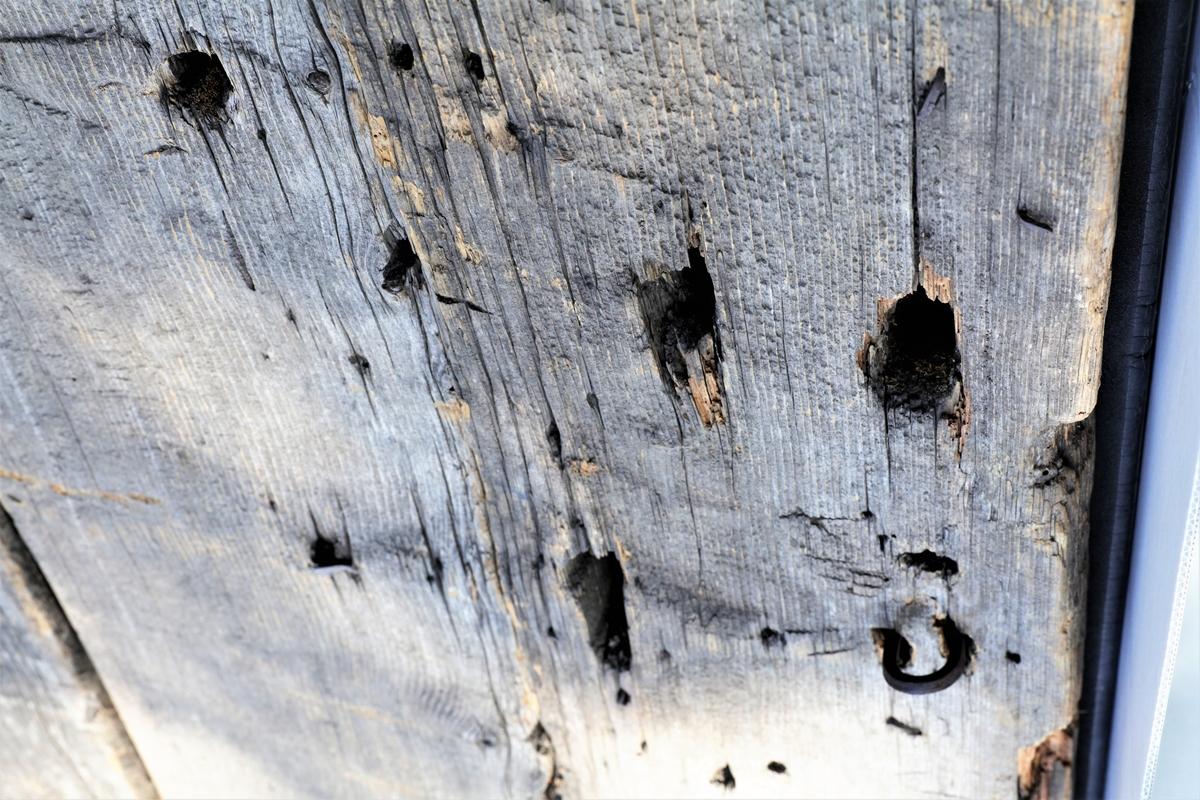 Dør fra Dyste kapell. Den er satt sammen av tre planker og har profilerte beslag på tvers. Døra er defekt på baksida. Det er slått på to nye filer.