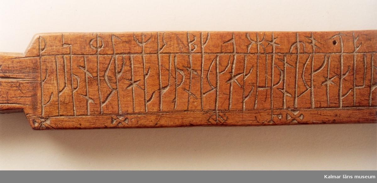 KLM 7775. Runstav. Trä. Platt fyrsidig med svärdfästeliknande handtag. Kalendern uppritad med runorna på bredsidorna och figurerna på smalsidorna.