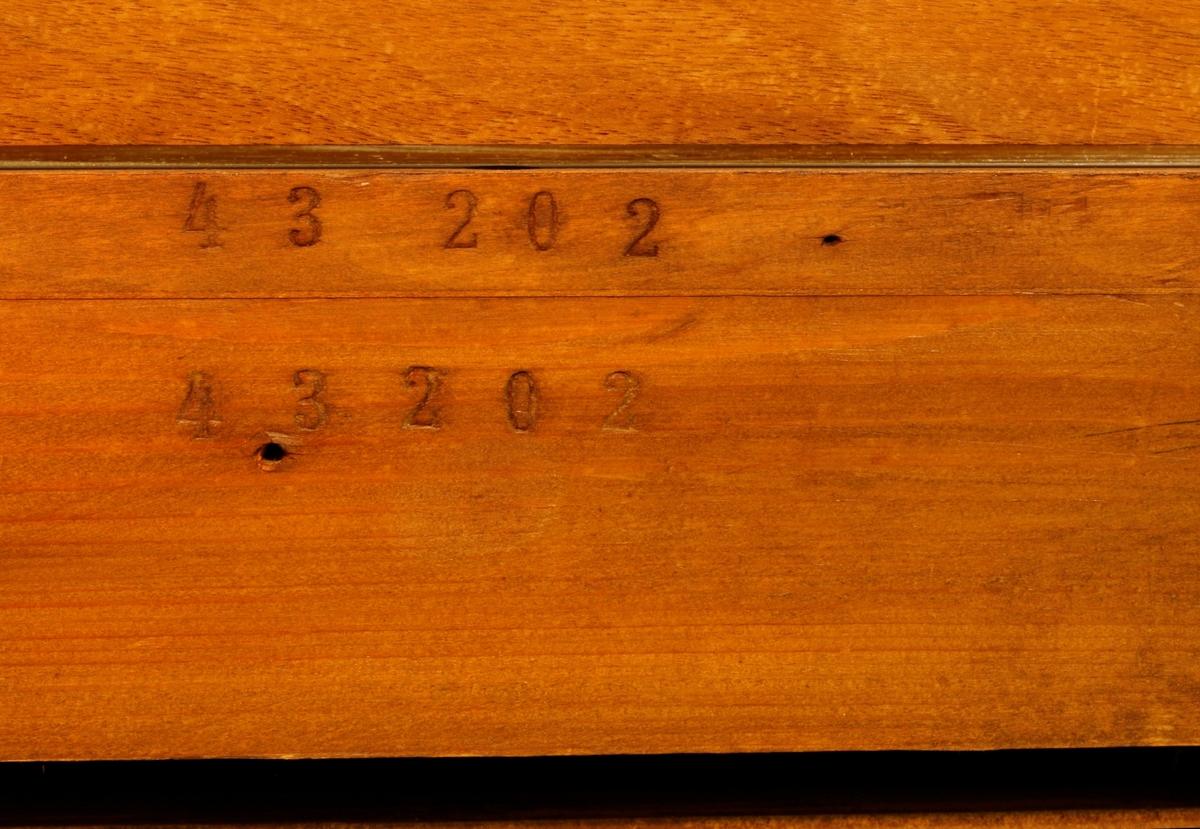 """Omfang: FF-f''' (5 oktaver) Høy kasse finert med nøttetrefiner. Profillister svart. Under klaviaturen er 6 firkanter utskjæret av sargen, som er foret med rødt tekstil. Klaviaturlokket lukkbar med en skyvbar skrå treplate. Notestativet er fastmontert i midten over tastaturet. Bak notestativet befinner seg en treplate, omkranset av et i midten med utskjæringer dekorert """"gelender"""".   10 register (se påskrift). Et ekstra tastatur med små taster over det ordinære tastaturet, der de svarte og hvite tastene er gruppert med regelmessig avveksling svart, hvit, svart, hvit osv.. Når en tast presses ned spilles en akkord (tonika, subdominant, dominant etc), en treklang i ulike posisjoner (smal, bred etc).  Over det lille tastaturet befinner seg en nummerering for de ulike akkordene og posisjonene. Det ekstra tastatuet kan skyves sideveis, totalt tretten trinn, slik at akkordene kan bli transponert til valgfri tonart (se bilde med skilt """"G, As, A, .... E, F, Fis, G"""").   Systemet ligner på det for Transponeringsapparat (RMT 93/7) av samme fabrikat, men med noe annerledes design for funksjons-tastene."""